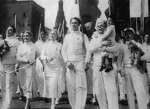 Marion, her son, and Martinov proudly march with other Soviets garbed in white (Circus)